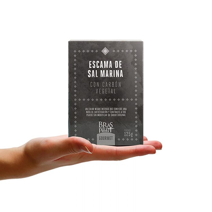 Caja de escama de sal marina con carbón 125 g vista frontal sobre mano