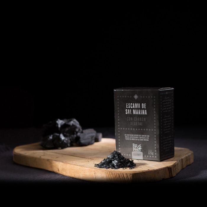Bodegón con escama de sal marina con carbón fondo oscuro