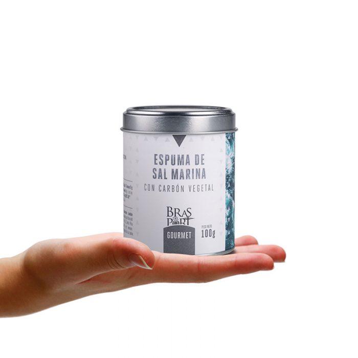 Bote de espuma de sal marina con carbón 100 g sobre mano
