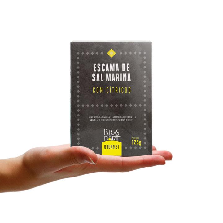 Caja de escama de sal marina con cítricos 125 g vista frontal sobre mano