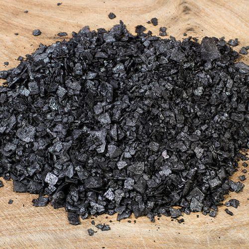 Textura de la escama de sal marina con carbón sobre madera