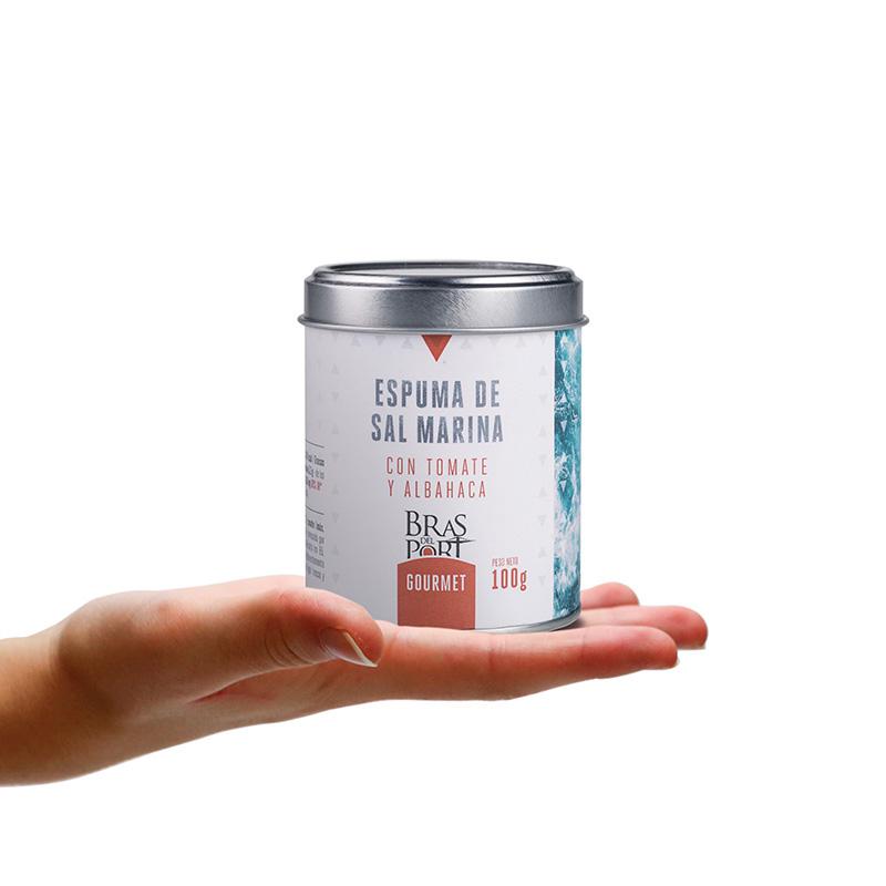 Bote de espuma de sal marina con tomate y albahaca 100 g sobre mano